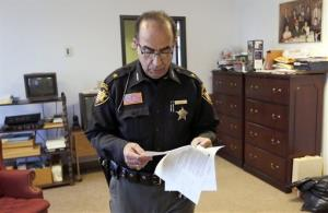 Jefferson County Sheriff Fred Abdalla brings printouts of an anonymous Facebook post in which he was threatened into his office on Wednesday, Jan. 9, 2013, in Steubenville, Ohio.