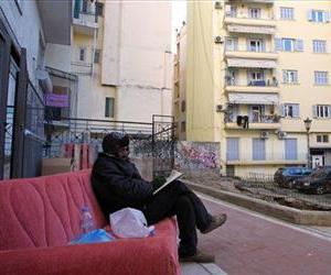 A homeless man sits on an old sofa on a pedestrian street in the northern port city of Thessaloniki , Greece, Jan. 7, 2013.