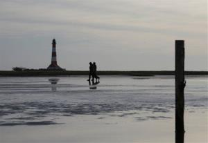 People stroll through the mud flats of the North Sea nearby Westerhever, northern Germany, as temperatures reach three degrees Celsius (37.4 Fahrenheit) on Saturday, Jan.14, 2012.