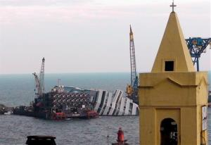 The cruise ship Costa Concordia, leaning on its side, is framed by a church bell tower in the Tuscan island of Giglio, Italy, today.