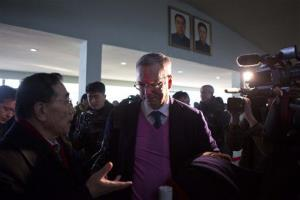 Google Chief Executive Eric Schmidt, center, is surrounded by journalists as he walks into the Pyongyang International Airport in Pyongyang, North Korea, on Thursday, Jan. 10, 2013.
