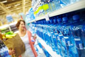 A shopper peruses the bottled-water section.