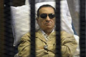 In this June 2, 2012 file photo, Egypt's ex-President Hosni Mubarak lays on a gurney inside a barred cage in the police academy courthouse in Cairo, Egypt.