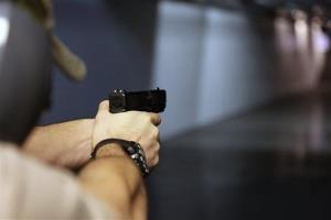 In this Jan. 4, 2013, photo, a man fires a hand gun at Sandy Springs Gun Club and Range, in Sandy Springs, Ga.