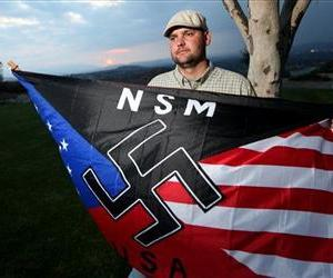 In this Oct. 22, 2010 file photo, Jeff Hall, who was killed by his son, holds a Neo Nazi flag while standing at Sycamore Highlands Park near his home in Riverside, Calif.