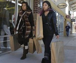 Shoppers carry bags as they make their way through a Houston area outlet mall, Dec. 20, 2012.