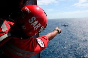A member of Venezuela's National Civil Aviation Institute points toward the ocean during the search for the plane, which went missing near Los Roques, Venezuela.