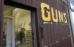 Rifles line a wall above in front of people standing in a gun shop.