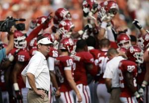 In this photo, Oklahoma head coach Bob Stoops looks on as his team huddles up before an NCAA college football game against Texas at the Cotton Bowl in Dallas.