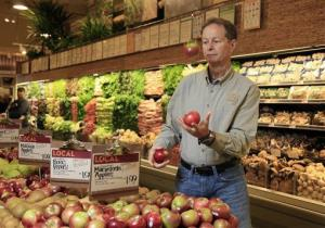 In this Nov. 18, 2009 photo, Whole Foods CEO John Mackey juggles apples as as he's photographed in one of his stores on New York's Upper West Side.