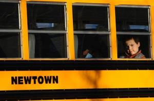 A boy sits on a Newtown bus leaving the new Sandy Hook Elementary School after the first day of classes in Monroe, Conn., Thursday, Jan. 3, 2013.