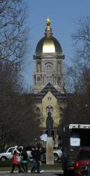 People walk in front of the Notre Dame administration building, known as the Golden Dome, Thursday, in South Bend, Indiana.