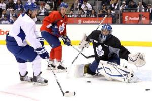 Toronto Maple Leafs Phil Kessel, left,  shoots on goalie James Reimer, right,  as Leo Komarov looks on during an NHL hockey training session at the Air Canada Centre in Toronto, yesterday.
