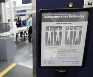 A sign describes what TSA officers see on their computer screens as volunteers go through the first full body X-ray scanner installed at O'Hare International Airport in Chicago.