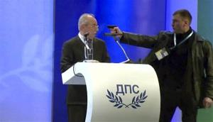 A man identified as Oktai Enimehmedov, 25, points a weapon at Ahmed Dogan, left, during his speech at his party's congress in Sofia, on Saturday Jan. 19, 2013.