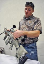 Steven Collis explains the optics on a HK-91 .308 rifle on Saturday, Jan. 19, 2013, at the Gun and Knife Show at the Julian Carroll Convention Center in Paducah, Ky.