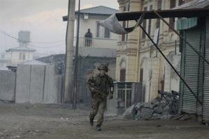 A Norwegian soldier with the NATO-led forces runs near the Kabul traffic police headquarters during today's attack.