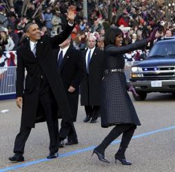President Barack Obama and first lady Michelle Obama wave as they walk down Pennsylvania Avenue in Washington, Monday, Jan. 21, 2013, during the Inaugural Parade.