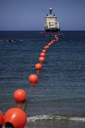 A fiber-optic cable to Cuba, suspended from buoys, is rolled out by a specialized ship off the Venezuelan coast.