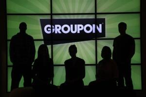 Groupon employees pose by the company logo in the lobby of the online coupon company's Chicago offices.
