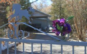 A bouquet of flowers adorns the entrance to a home where a couple and their three young children were found shot to death south of Albuquerque.