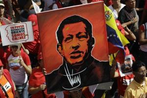 A supporter of Venezuela's President Hugo Chavez holds up a painting of him during a symbolic inauguration rally for Chavez outside Miraflores presidential palace in Caracas, Venezuela, Jan. 10, 2013.