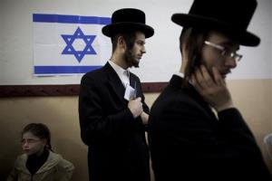 An Ultra-orthodox Jewish man holds his ID card as he waits to vote in Bnei Brak, Israel.