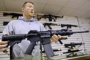 This file photo shows a gun store owner with an AR-15 rifle.