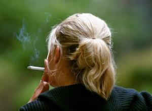 In this file photo, a woman smokes a cigarette during a break from work in downtown Chicago.