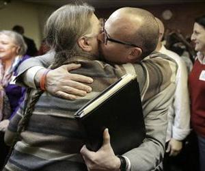 C. Kelly Smith, of Providence hugs Patrick Crowley, of Lincoln after a house committee vote on gay marriage at the Statehouse, in Providence, Jan. 22, 2013.