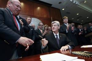Rep. Gary Chism, left, is offered a pen by Mississippi Gov. Phil Bryant after he signs a new state law to boost the state's business climate.