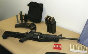 This March 27, 2006 file photo, shows a Bushmaster AR-15 semi-automatic rifle and ammunition on display at the Seattle Police headquarters in Seattle.