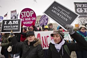 Anti-abortion protesters and supporters of legal abortion stand in front of the Supreme Court Friday.