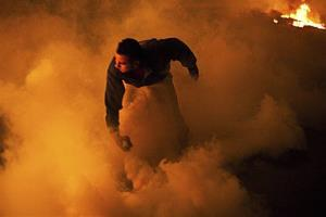 In this Sunday, Jan. 27, 2013 photo, a protester prepares to throw a rock while surrounded by tear gas and smoke during clashes with security forces near Tahrir Square in Cairo, Egypt.