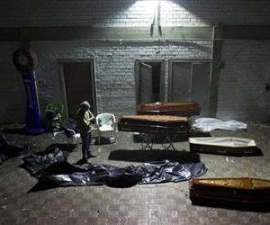 A man stands around coffins containing the remains of victims after the bodies were identified at a gymnasium in Santa Maria city, Rio Grande do Sul state, Brazil, Jan. 27, 2013.