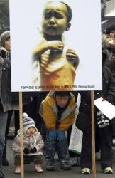 South Korean children watch the progress from under a picture of a North Korean child suffering from famine during a rally in Seoul, South Korea, Friday, Jan. 27, 2012.