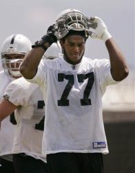 Oakland Raiders tackle Kwame Harris, who used to play for the San Francisco 49ers, puts on his helmet during Raiders football minicamp at Raiders headquarters  in this 2008 photo.