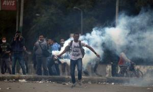 A protester with Arabic writing on his shirt that reads, down down, with the rule of the supreme leader, throws a tear gas canister at riot police near Tahrir Square, Cairo, Egypt, Jan. 28, 2013.