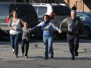 In this photo provided by the Newtown Bee, a police officer leads two women and a child from Sandy Hook Elementary School in Newtown, Conn.