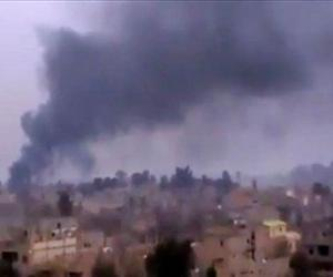 Smoke rises from heavy shelling in Deir el-Zour, Syria, Jan. 28, 2013.