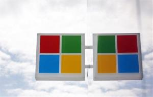 The new Microsoft logo is seen reflected in windows at a company store Thursday, Aug. 23, 2012, in Seattle.