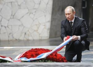 Vladimir Putin adjusts a ribbon as he lays a wreath at the Eternal Flame while visiting the Battle of Stalingrad memorial, ahead of May 9 Victory Day, in Volgograd, formerly Stalingrad, May 6, 2011.