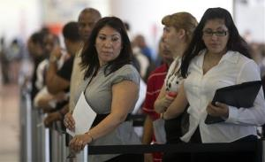 In this Tuesday, Jan. 15, 2012, photo,  Norma Urbario, left, and America Rodriguez stand in line, holding their resumes, during the job fair that the Miami Marlins hosted at Marlins Park in Miami.