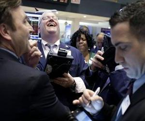 A trader laughs while working on the floor of the New York Stock Exchange in New York, Thursday, Jan. 31, 2013.