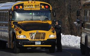 A police officer greets a bus at the entrance to a school on the first day of classes after the holiday break in Newtown, Conn., on Jan. 2.