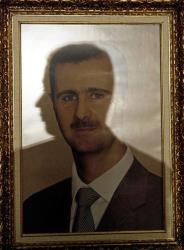 The profile of a Syrian embassy employee is reflected in a framed image of Bashar al-Assad at a local Venezuelan hotel, in Caracas, Tuesday, Nov. 27, 2012.