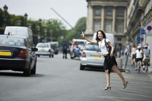 A woman hailing a cab in Paris.