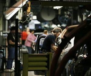 In this Jan. 28, 2013 photo, workers assemble cars along a line at the General Motors Fairfax plant in Kansas City, Kan.