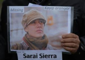 A member of the Istanbul-based Association For Families With Lost Relatives hands out flyers with photos of Sarai Sierra in Istanbul, Turkey, Thursday, Jan. 31, 2013.