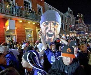 Fans hoist a sign of Baltimore Ravens' Ray Lewis as they walk down Bourbon Street while celebrating the Ravens' victory in Super Bowl XLVII in New Orleans, Feb. 3, 2013.